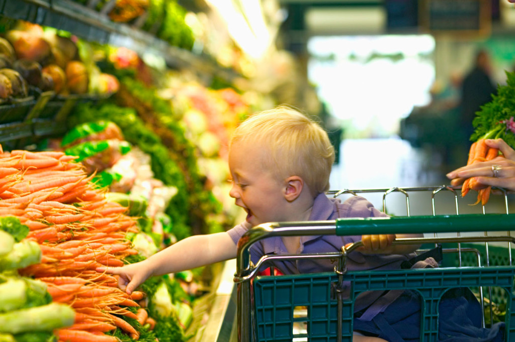 Toddler boy reaching for carrots in grocery store