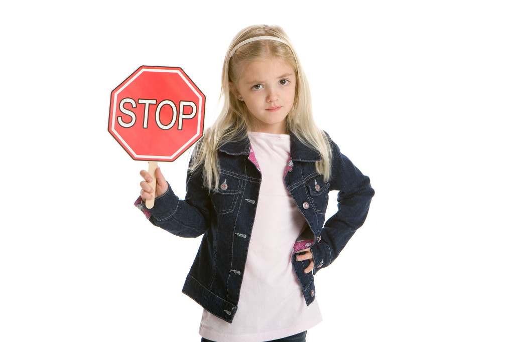 Cute little girl isolated, holding a stop sign