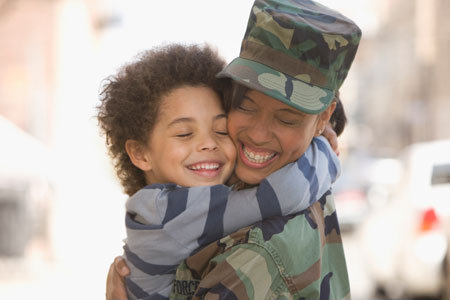 Excited returning soldier hugging her son